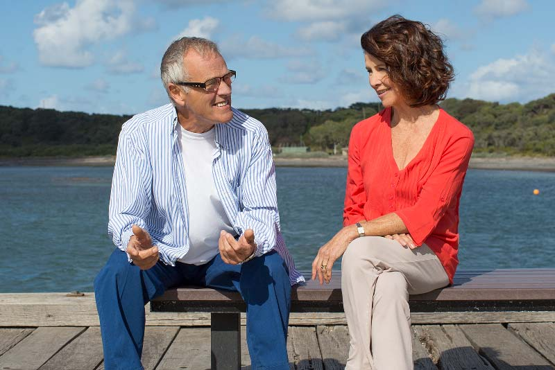 Couple with hearing loss and aids at pier