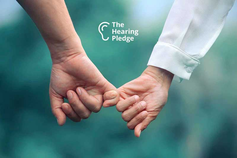 Holding hands give a hearing pledge hearing aids
