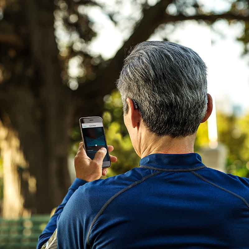 Man using Widex Beyond iPhone app in the park running