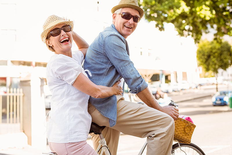 man and woman on bicycle with hearing aids