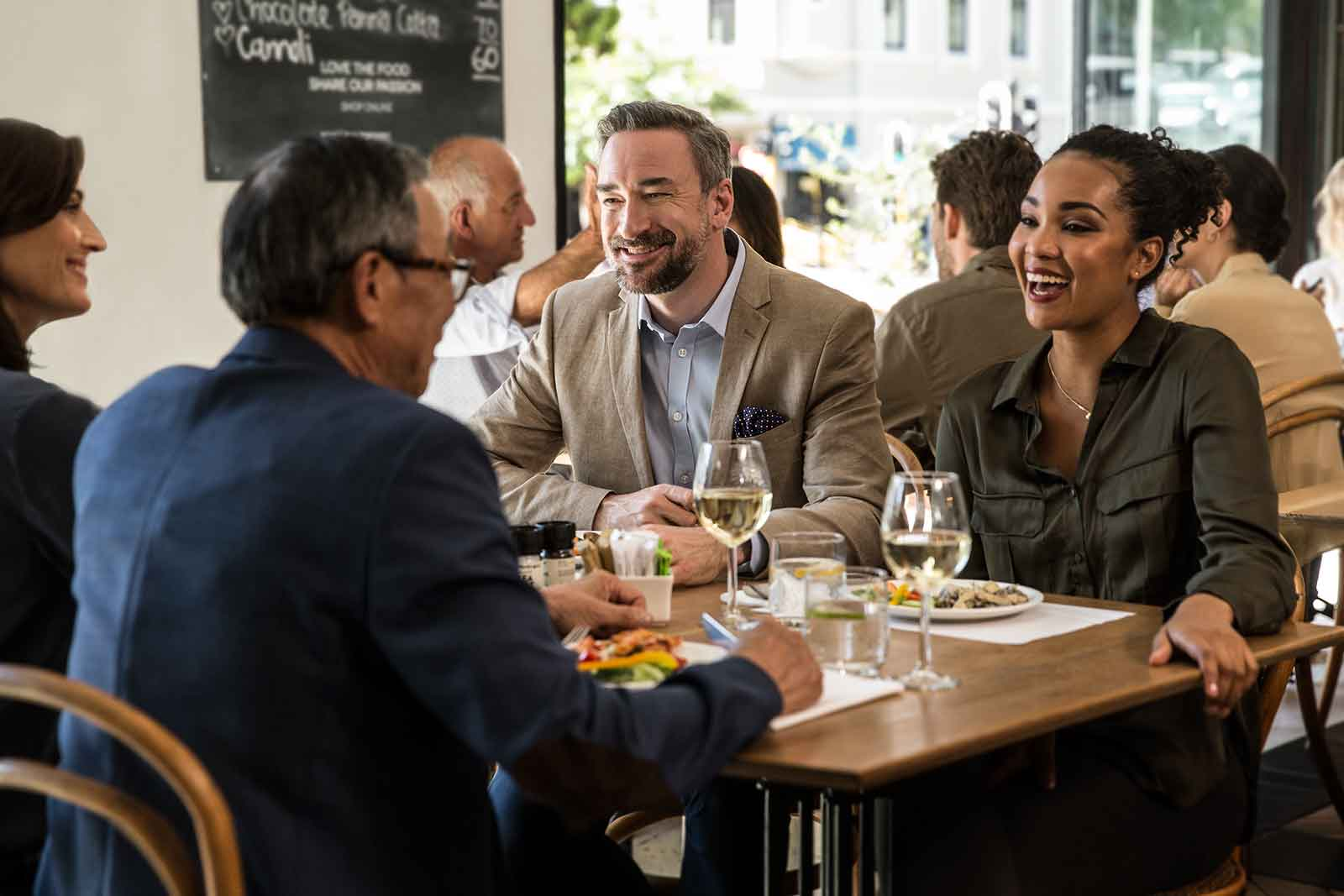 Man wearing hearing aids having lunch with friends in a noisy restaurant